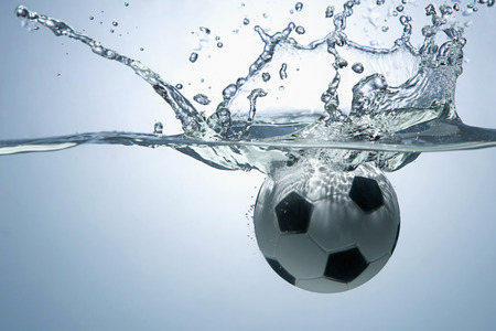 bliss: Soccer ball splashing into water Stock Photo