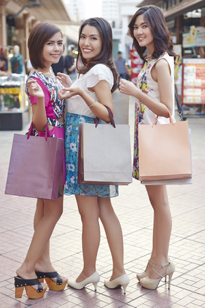 only three people: Young women posing while holding shopping bags