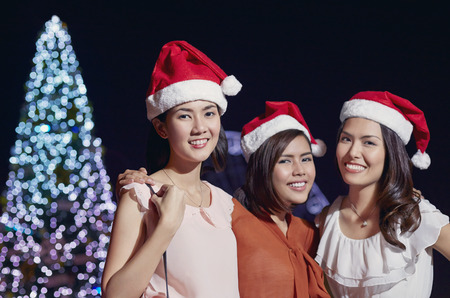 wearing santa hat: Young women wearing Santa hat celebrating Christmas festival