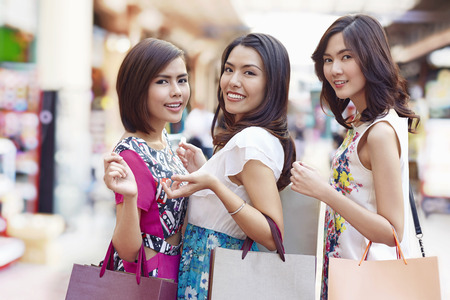 three people only: Young women posing while holding shopping bags