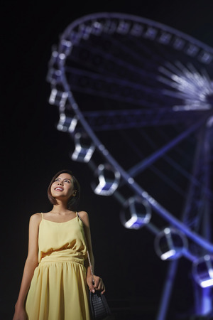 south asian ethnicity: Young woman posing with ferris wheel at the back Stock Photo