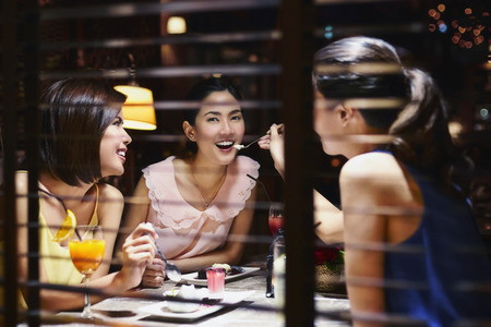 若い女性が彼女の友人のデザートのスプーンを供給 写真素材