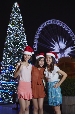wearing santa hat: Young women wearing Santa hat celebrating Christmas festival