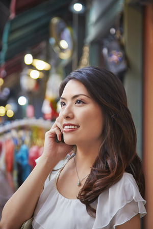 south asian ethnicity: Young woman on the phone smiling Stock Photo