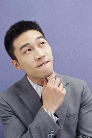 wondering: Wondering businessman touching his chin