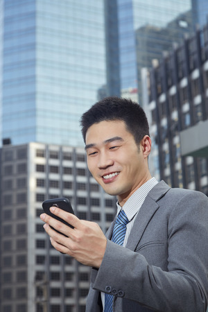 handphone: Businessman looking at his phone Stock Photo
