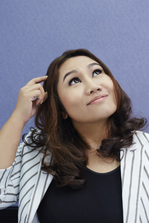 south asian ethnicity: Businesswoman thinking while scratching head