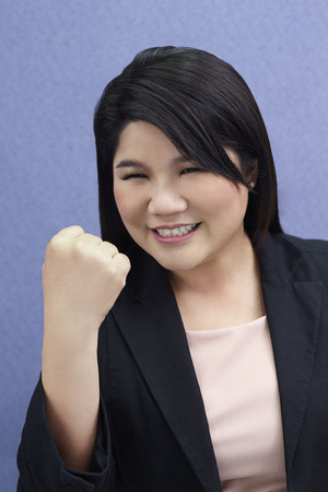 pumping: Businesswoman cheering while fist pumping Stock Photo