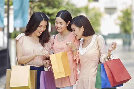 three people only: Young women checking their shopping bags