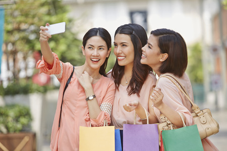 Young women taking photograph together