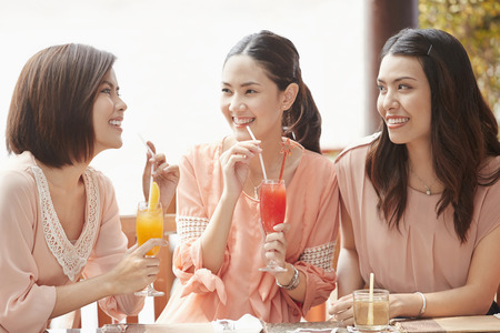south asian ethnicity: Young women having a drink together Stock Photo