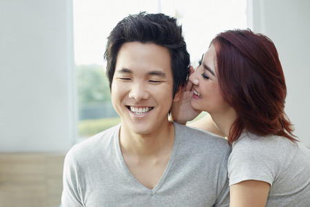 south asian ethnicity: Girlfriend whispering to her boyfriend Stock Photo