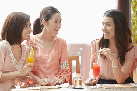 three people only: Young women having a drink together Stock Photo
