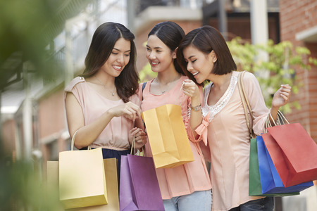 south asian ethnicity: Young women checking their shopping bags