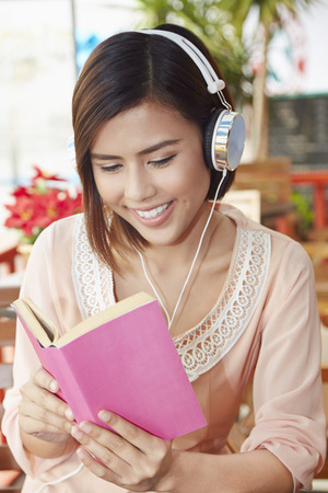 south asian ethnicity: Young woman reading a book while listening to music