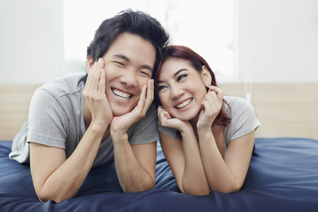south asian ethnicity: Couple lying on the bed, looking at each other