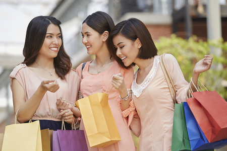 only three people: Young women checking their shopping bags