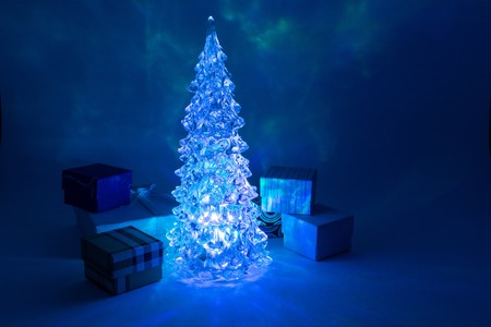 christmas tree toy shining with a beautiful shadow northern lights background near gift boxesand highlights in