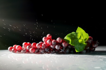 grape: grapes in the sun with splashes of water on a dark background