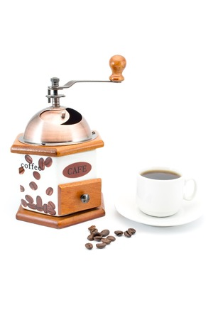 macchiato: grinder next to a cup of coffee and beans isolated on white background