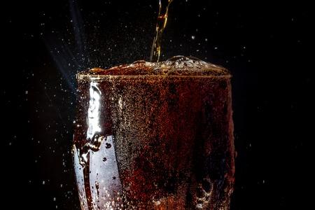 pocima: Soda gran vaso, vaso desbordante de refresco de cerca con burbujas aisladas sobre fondo negro