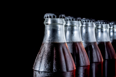 Soda glass bottles isolated on black background