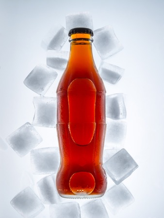 Soda glass bottle in a refrigerated with ice cubes on a light background. Top view. Stock Photo