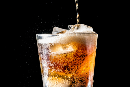 Stream of soda being pouring into a glass with soda and ice cube on black background, closeup texture, splashing, splash, fizz