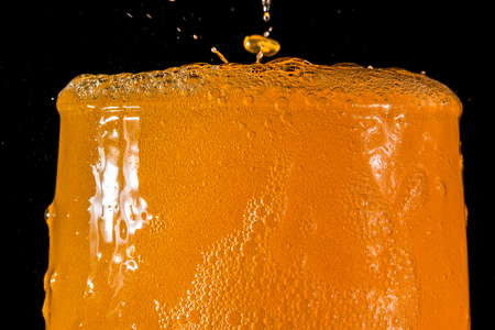 Orange soda large glass, overflowing glass of orange soda closeup with bubbles isolated on black background Stock Photo