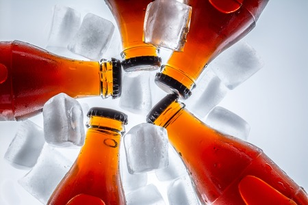 Soda glass bottles in a refrigerated with ice cubes on a light background. Top view.