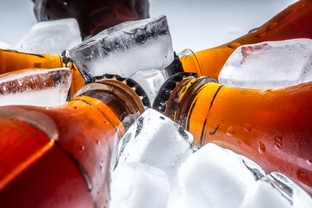 refrigerated: Soda glass bottles in a refrigerated with ice cubes on a light background Stock Photo