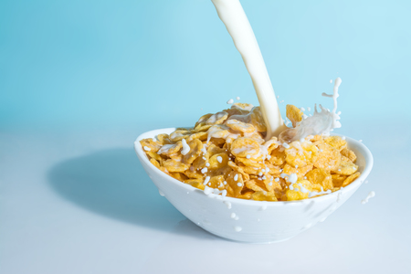 Milk stream jet pouring into a bowl with yellow flakes, milk splashes on a light blue celestial background