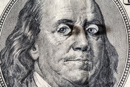 Ben Franklins face with drops of water on eyes on the old US $100 dollar bill macro.