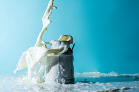 Splash of milk, stream of milk pouring into a overflowing can of milk on a light blue celestial sky background
