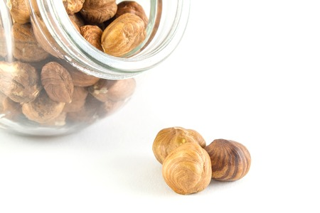 hazelnuts in a glass jar isolated on white background