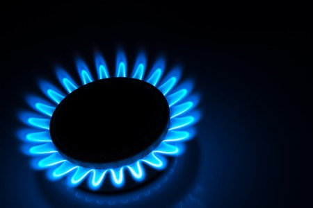 butane: burning gas stove hob blue flames close up in the dark on a black background