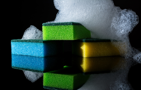 Colorful sponges with foam and reflection, bubbles, isolated on black background