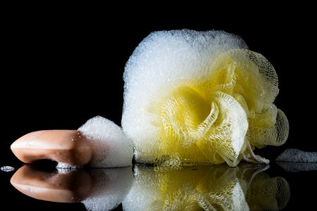 Yellow sponge body with foam near soap with reflection isolated on black background