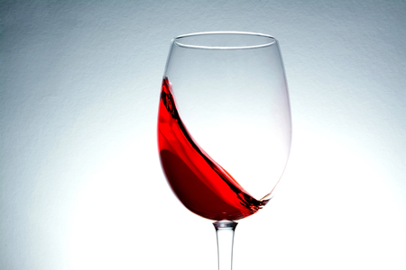 red wine in glass, splashing, splash, wave of red wine close up