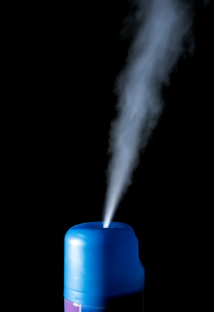 Blue spray air freshener in motion isolated on a black background