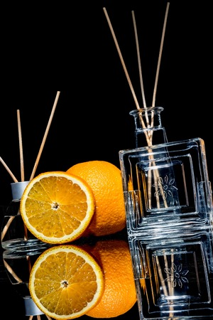 Air fresheners with orange fruits scent in a beautiful glass jars with sticks and whole orange and a slice of orange with reflection isolated on a black background