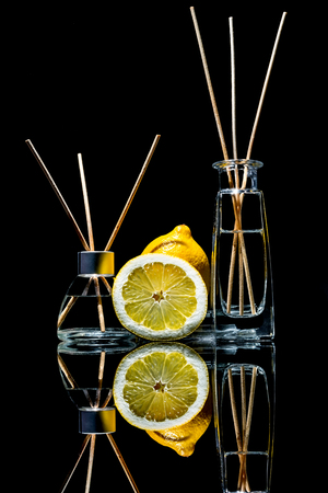Air fresheners with lemon scent in a beautiful glass jars with sticks and whole lemon and a slice of lemon with reflection isolated on a black background