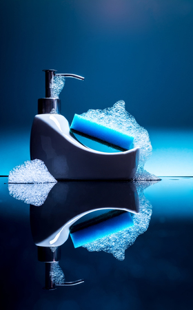 Tiny bath with a sponge and foam with reflection on a blue background, detergent