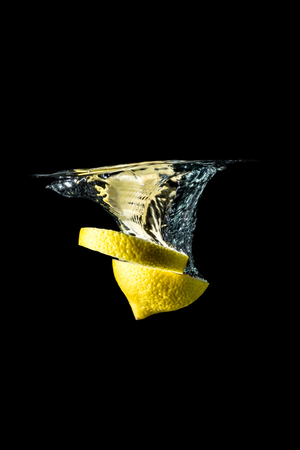 Lemon slices falling into the water close-up, macro, splash, bubbles, isolated on black background