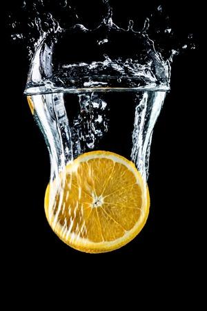 Orange slices falling into the water close-up, macro, splash, bubbles, black background Stock Photo