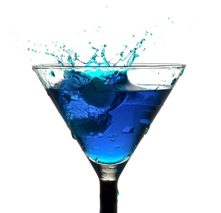 splashing out of the glass blue drink from falling ice cubes Stock Photo