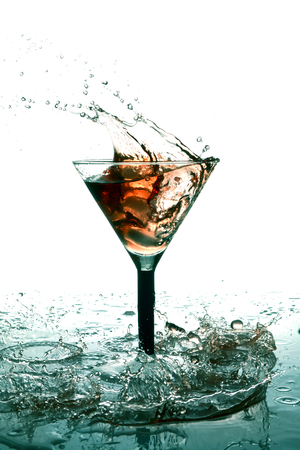 Ice cubes splashing in glass of alcohol and many drops and wave on table on white background
