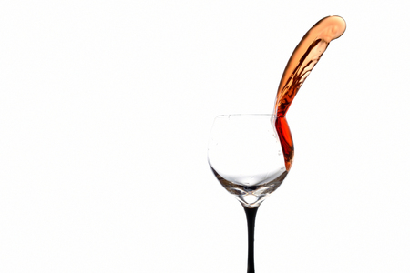 stream of wine being poured out off a glass isolated on a white background