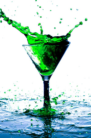 falling cubes: splash in a glass with a green drink alcohol