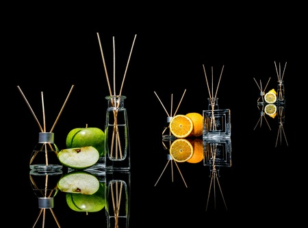 Air fresheners in a glass jars with sticks and lemon, green apple and orange with reflection isolated on a black background. Big large size.